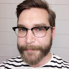 Emil Björklund, a guy with beard and glasses, in his thirties, wearing a striped sweater.